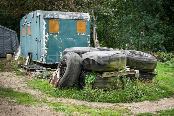A pile of old tyres in front of an abandoned caravan Stock photo © lucielang