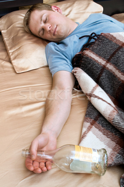 A young man sleeping on the couch with a bottle of wiskey Stock photo © luckyraccoon