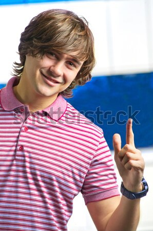 Stock photo: Happy young man indicating OK sign against the window