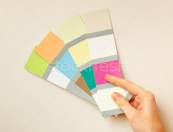 Hand holding color samples against wall. Stock photo © luckyraccoon