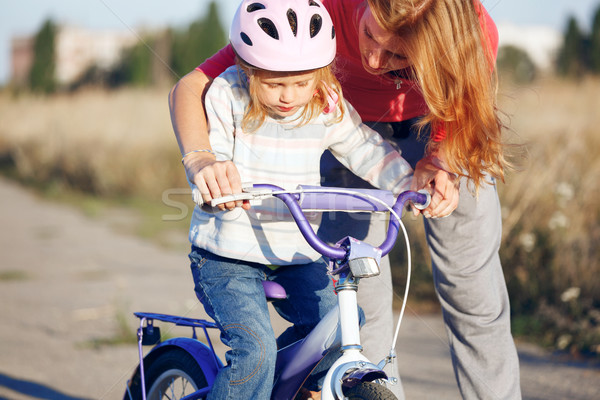 Redhead girl in helmet learning riding bike. Stock photo © luckyraccoon