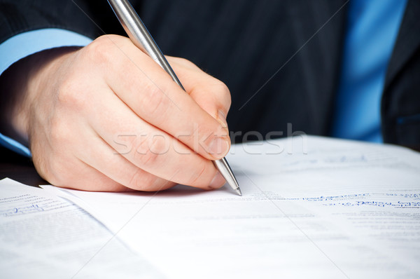 businessman with pen signing contract  Stock photo © luckyraccoon