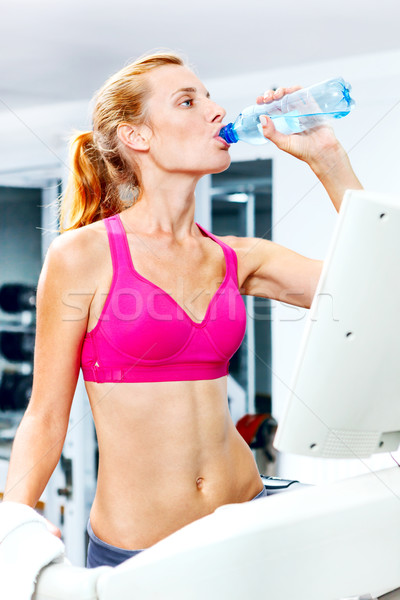 Young woman doing cardio on treadmill in a gym. Stock photo © luckyraccoon