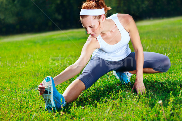 Young girl stretches before exercise in park Stock photo © luckyraccoon