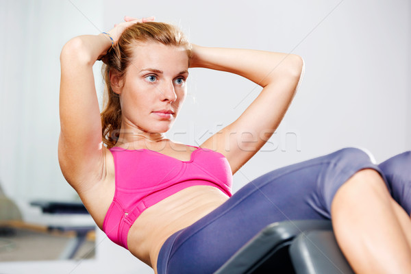 Beautiful young athletic woman doing sit-ups in a bench. Stock photo © luckyraccoon