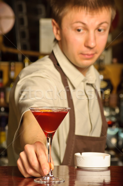 A barman holding the glass with cocktail Stock photo © luckyraccoon