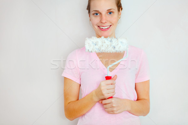 Happy Woman standing againtst wall with roller brush. Stock photo © luckyraccoon