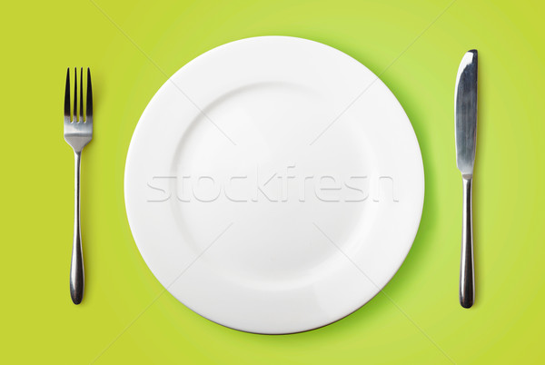 Empty plate, fork and knife on green background Stock photo © luckyraccoon