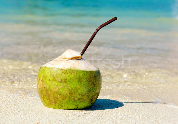 Opened coconut with a straw on summer beach  Stock photo © luckyraccoon