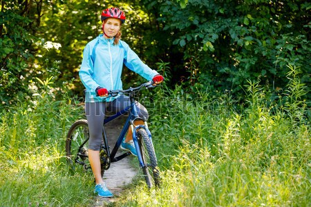 Young woman with mountain bike outdoors. Stock photo © luckyraccoon