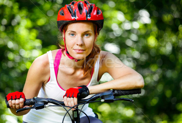 Happy Young woman leaned over the handlebars of her bike. Stock photo © luckyraccoon