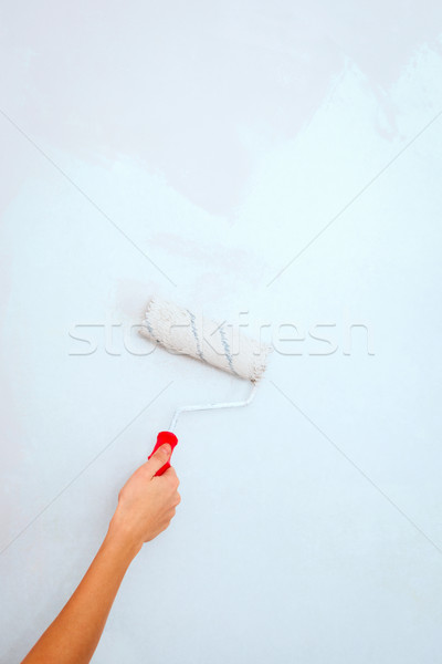 Hand with roller brush painting wall. Stock photo © luckyraccoon