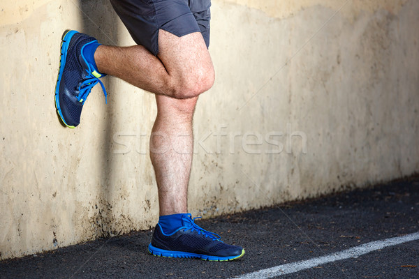 Male runner leaning relaxed against wall.  Stock photo © luckyraccoon
