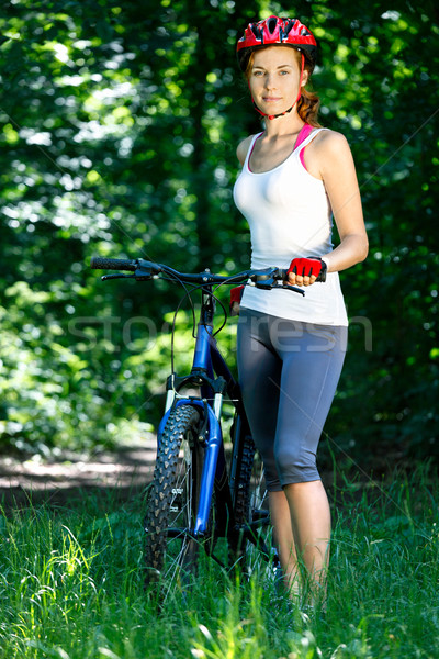 Portrait of happy young woman with mountain bike outdoors. Stock photo © luckyraccoon