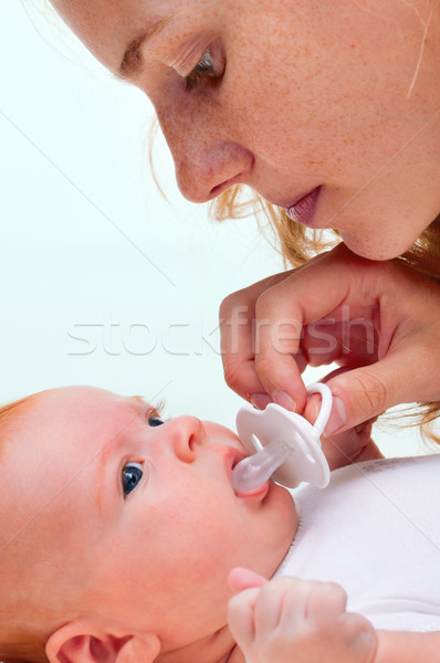 young mother trying to give baby`s dummy to her newborn baby Stock photo © luckyraccoon