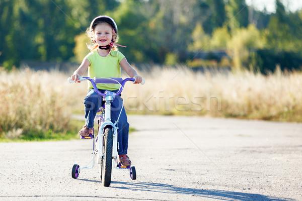 Small funny kid riding bike with training wheels. Stock photo © luckyraccoon