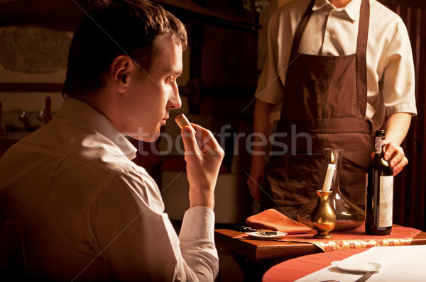 Man sniffing the cork of a wine bottle Stock photo © luckyraccoon