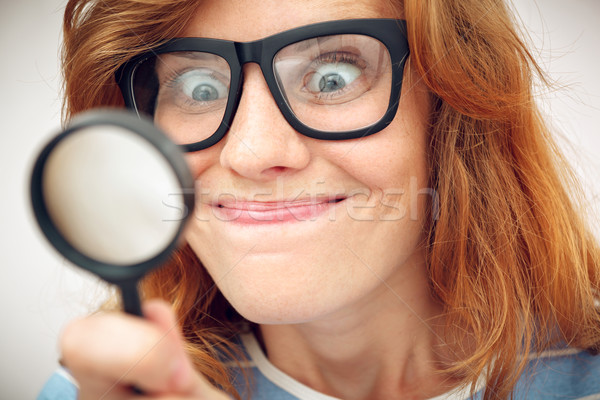 Young geek looking through magnifying glass. Stock photo © luckyraccoon