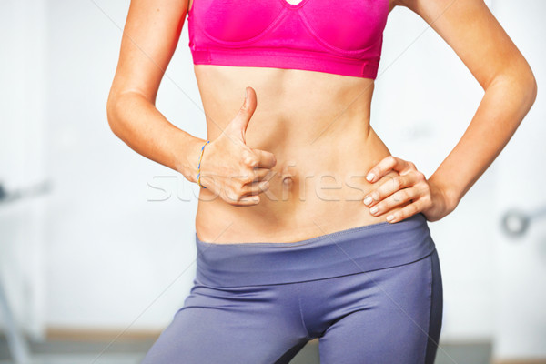 Closeup of young slim woman with six-pack torso. Stock photo © luckyraccoon