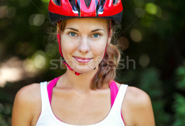 Stock photo: Portrait of happy young cyclist in sport clothes and helmet.