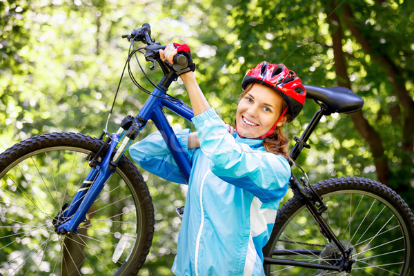 Portrait of young woman with mountain bike on shoulder. Stock photo © luckyraccoon