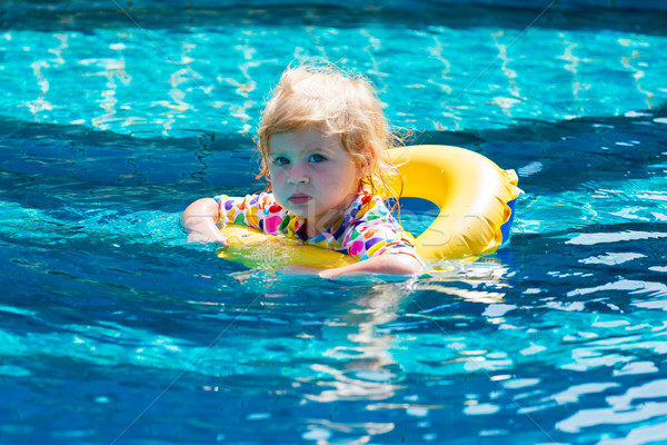 Little baby swimming in a pool on swimming ring Stock photo © luckyraccoon