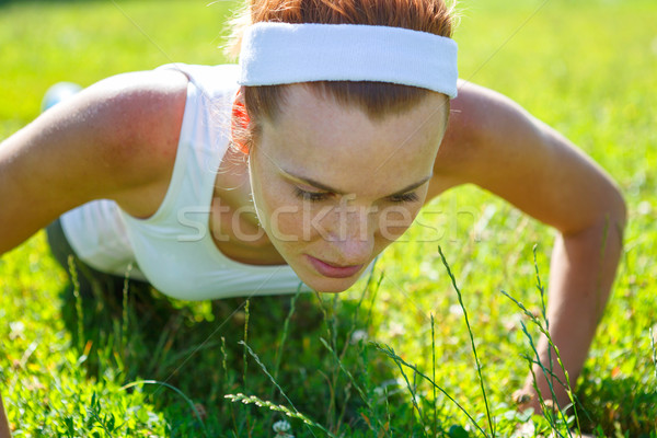 Young woman doing push ups on green grass. Stock photo © luckyraccoon