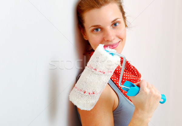 Happy woman with roller brush standing against wall. Stock photo © luckyraccoon