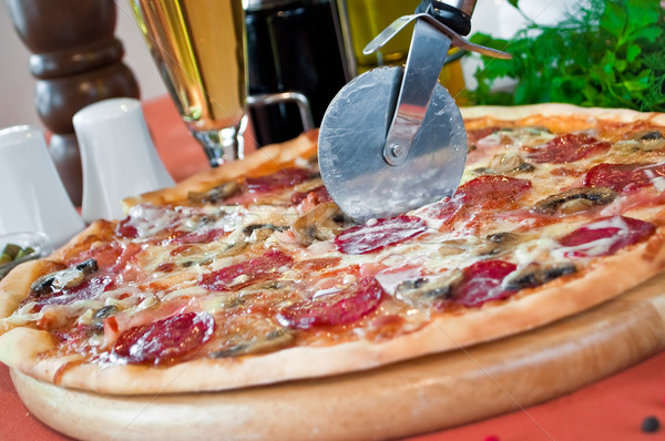Closeup of a pizza with salami and mushrooms Stock photo © luckyraccoon