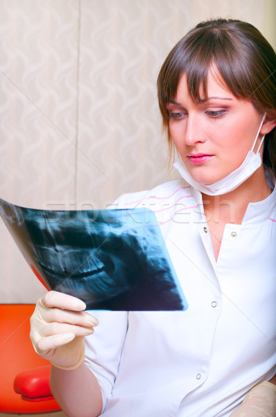 Young dentist looking at x-ray picture Stock photo © luckyraccoon