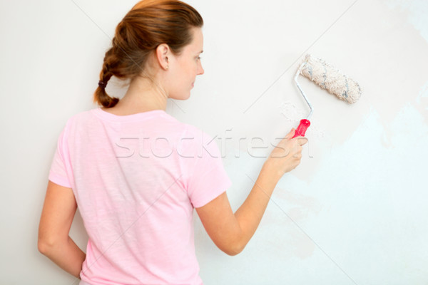 Young woman painting wall with roller brush. Stock photo © luckyraccoon