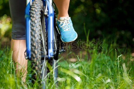Closeup  woman riding mountain bike outdoors. Stock photo © luckyraccoon