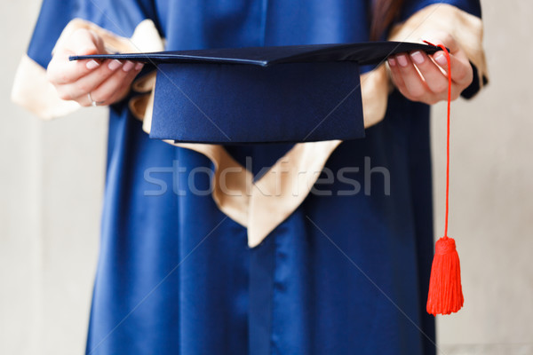 Young student holding academic hat in hands Stock photo © luckyraccoon