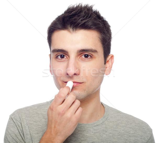 Jeune homme lèvre baume élégant isolé Photo stock © luissantos84