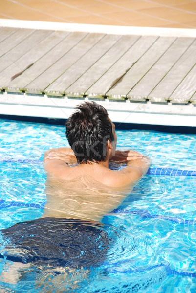 Young man relaxing at the edge of the swimming pool Stock photo © luissantos84