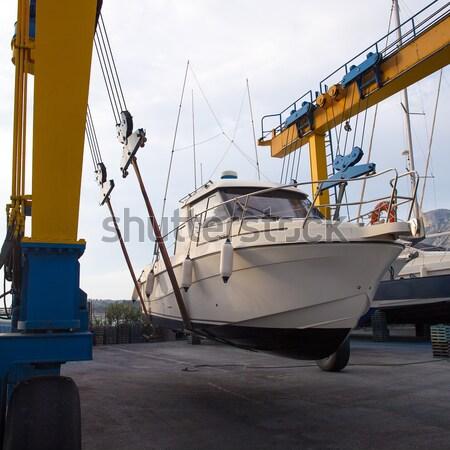 Dock crane elevating a fishing boat Stock photo © lunamarina