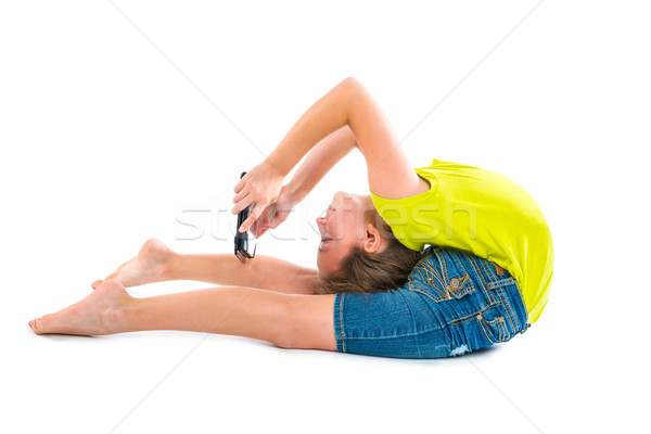 Flexible contortionist kid girl playing with tablet pc Stock photo © lunamarina