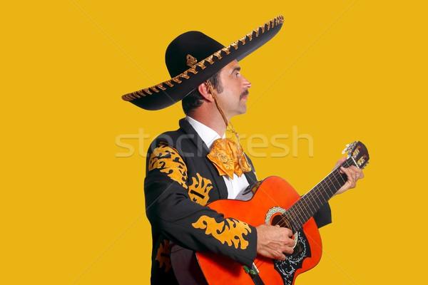 Charro Mariachi playing guitar on yellow Stock photo © lunamarina