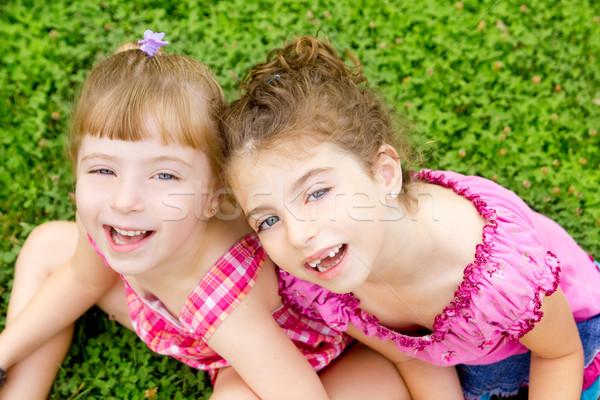 children girls laughing sit on green grass Stock photo © lunamarina