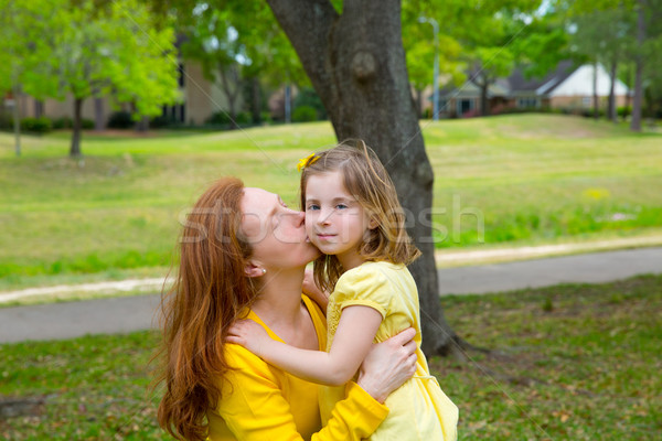 Mother kissing her blond daughter in green park Stock photo © lunamarina