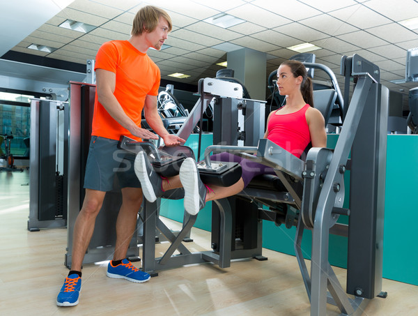 Gym woman leg extension with personal trainer Stock photo © lunamarina