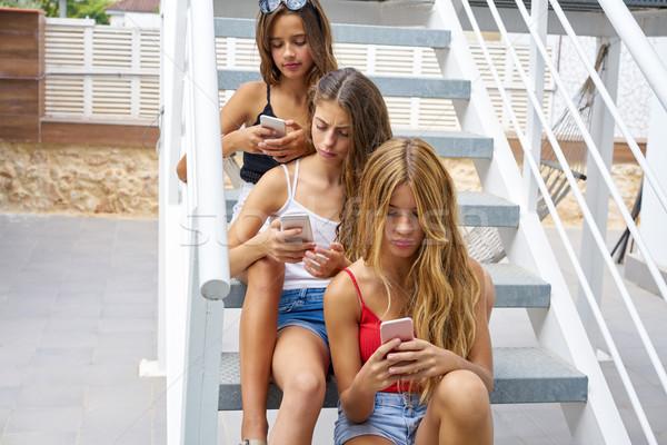 Teen best friends girls in a row with smartphone Stock photo © lunamarina
