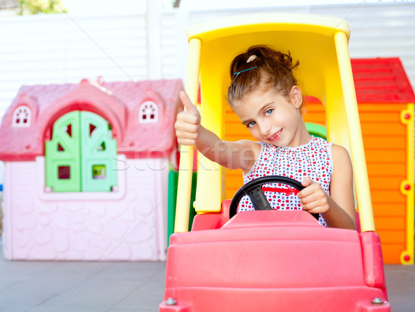 children girl driving a toy car with ok gesture Stock photo © lunamarina