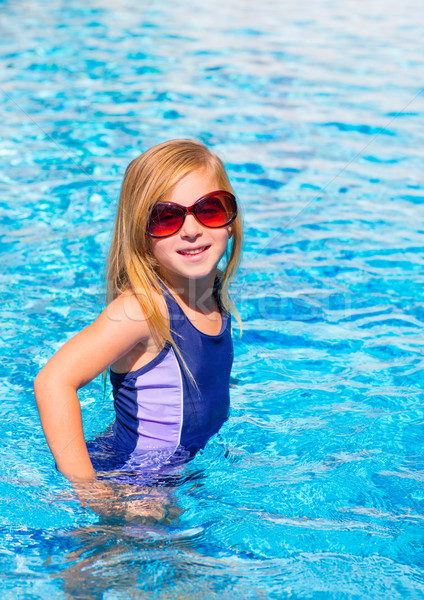 blond kid girl in blue pool posing with sunglasses Stock photo © lunamarina