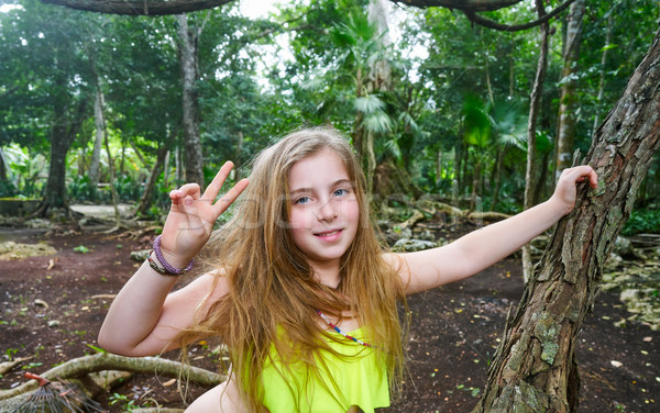 Caucasian girl playing victory sign in jungle Stock photo © lunamarina