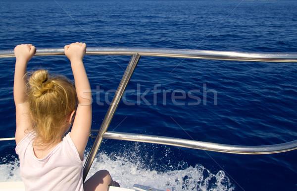 Blond little girl rear view sailing in boat Stock photo © lunamarina