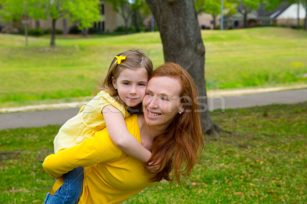 Daughter and mother piggyback smiling in park outdoor Stock photo © lunamarina