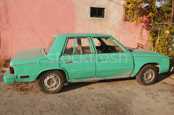 aged old vintage green car in pink wall Stock photo © lunamarina