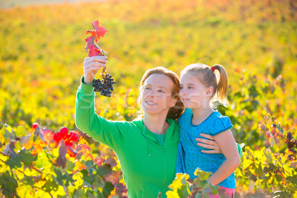 Stock photo: Mother and daughter on autumn vineyard smiling holding grape