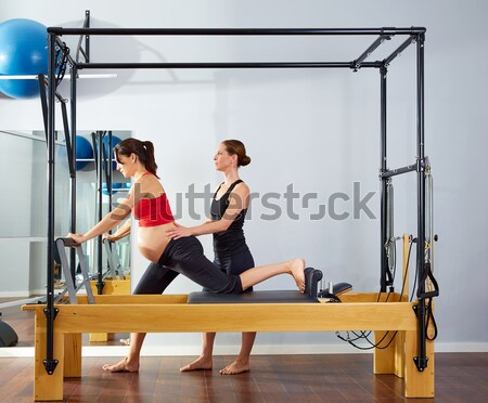 Pilates woman in cadillac legs split reformer Stock photo © lunamarina